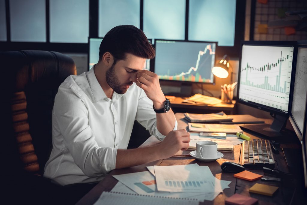 A data scientist at a top consulting firm stressed over the amount of data need to gather an analyze. His desk is cluttered with graphs while his screen has more graphs. He holds his nose as he takes a short mental destressing moment.