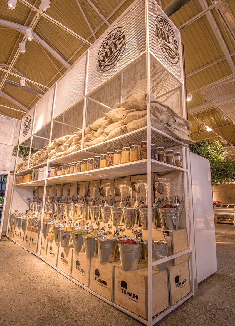 wooden shelve construction filled with jars and buckets of spices