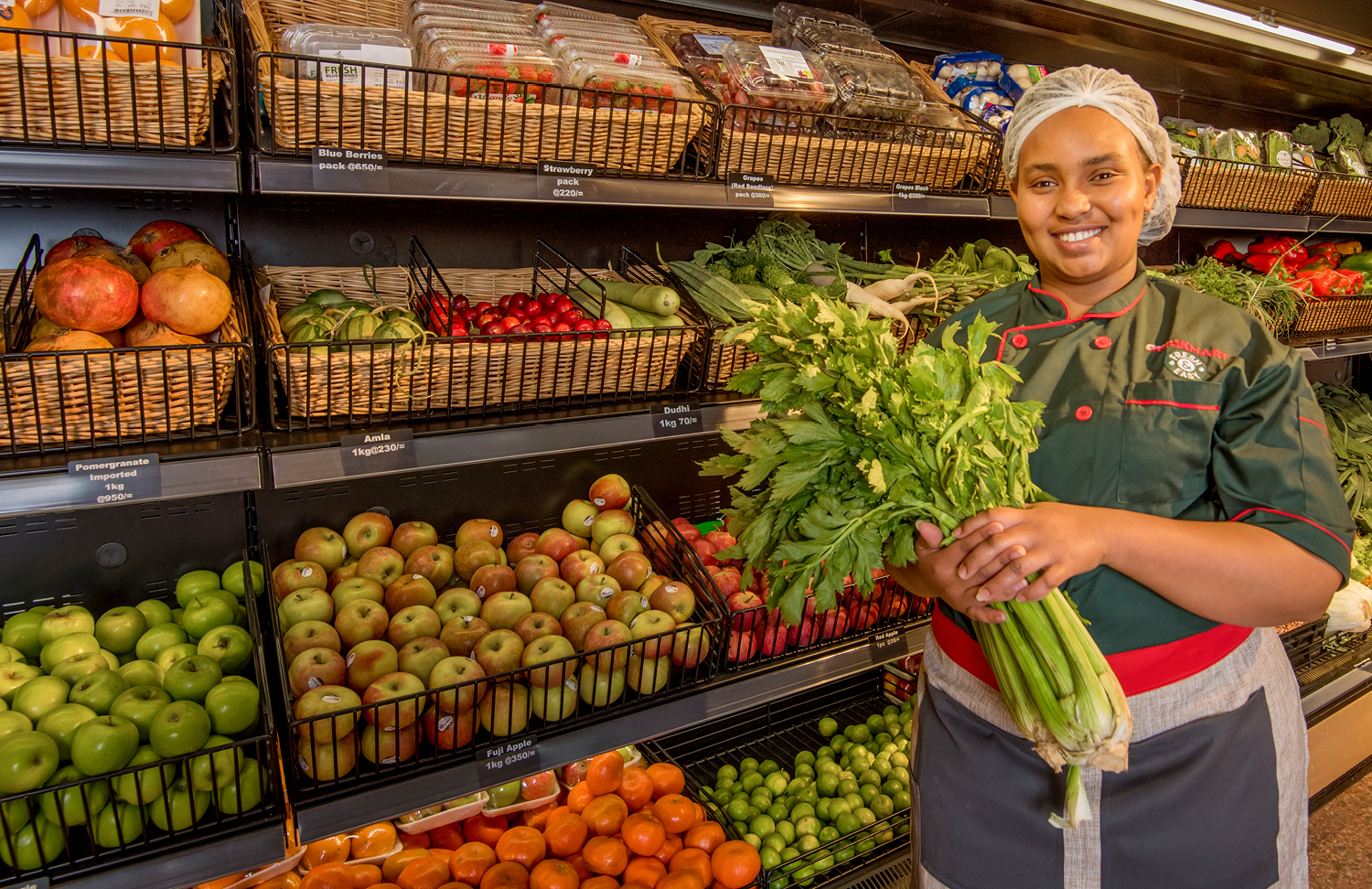 person holding vegetables in from of shelf full of fruit
