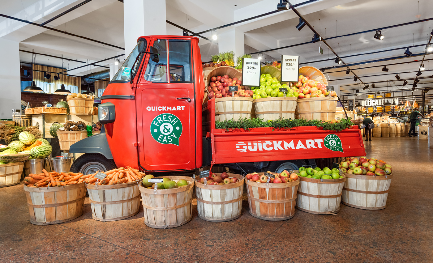 Beautiful supermarket with colourful fruits place in baskets and a red mini pickup truck from quickmart