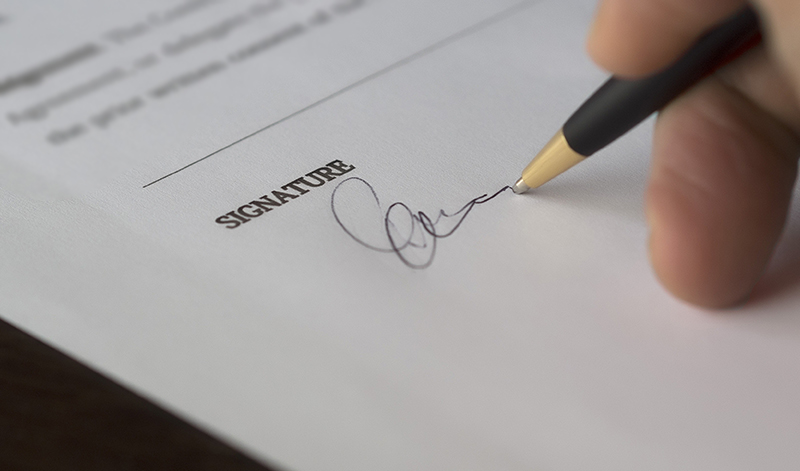 A pen signing a Will.