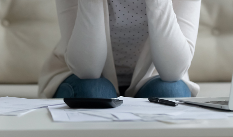 A woman looking at papers and feeling stressed.