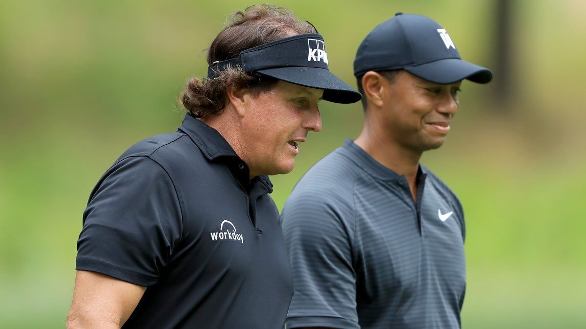 Tiger Woods and Phil Mickelson walk together on golf Course at 2020 Champions for Charity