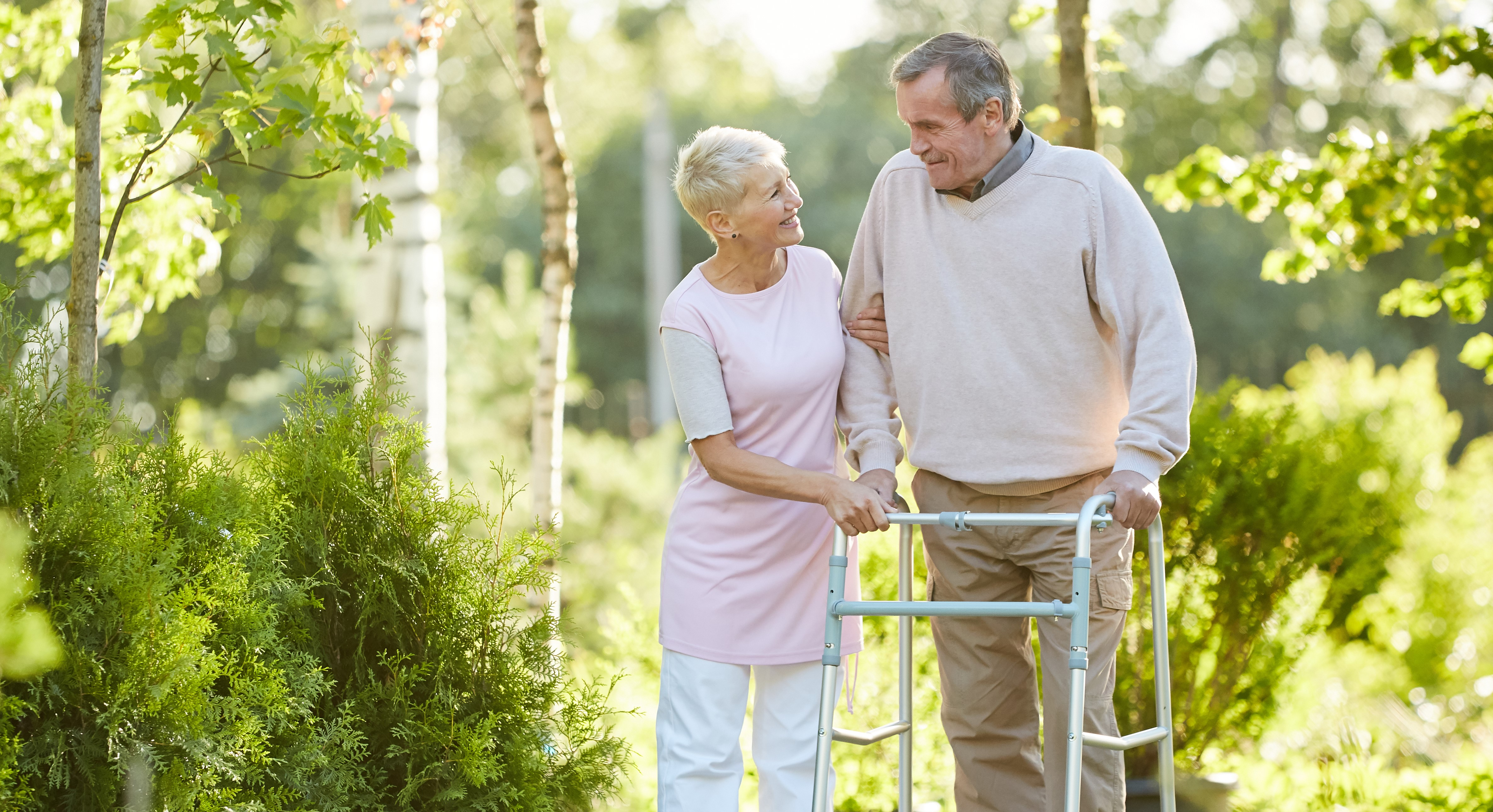 Woman walking with man after knee replacement surgery