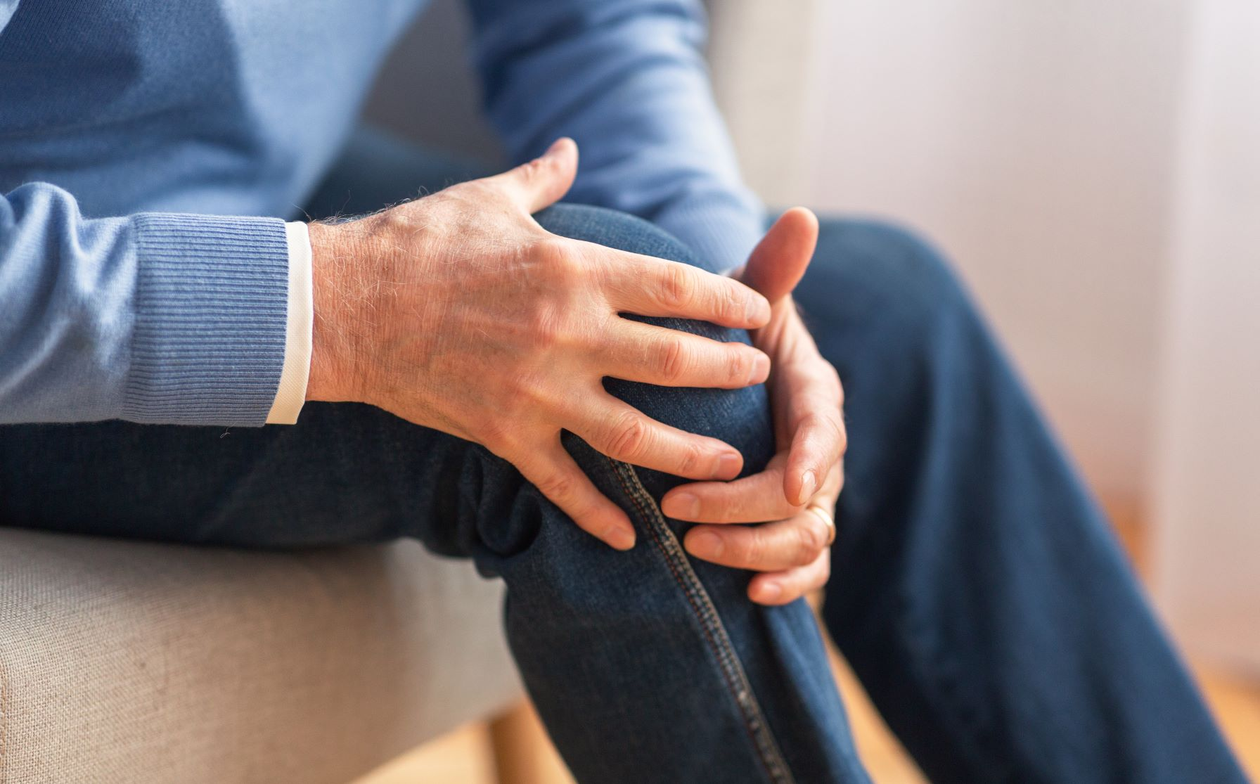 man sitting on couch holding his painful knee