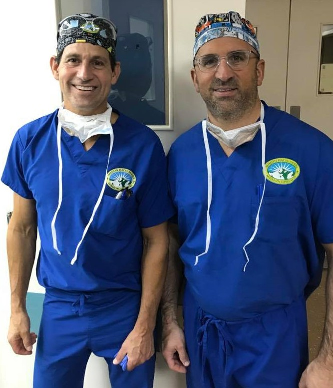 Cory Calendine, MD and fellow orthopaedic surgeon in scrubs standing in hospital hallway