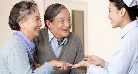 Nurse Assisting Elderly Couple with Hiring a Caregiver
