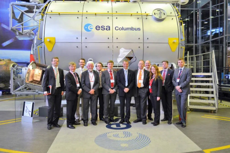 A delegation group photo posing in front of the European Space Agency Columbus satellite