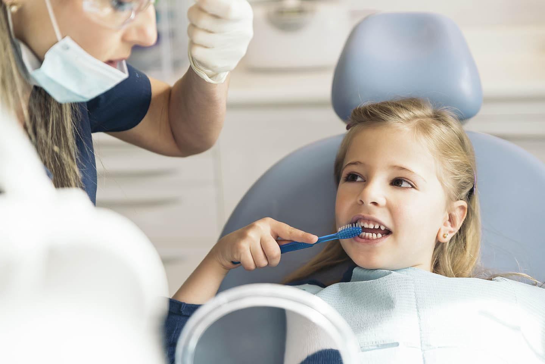 girl learning to brush teeth in dental chair
