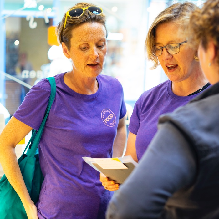 Cat and Angel from Brighton Food Tours discussing a food product with the shop owner