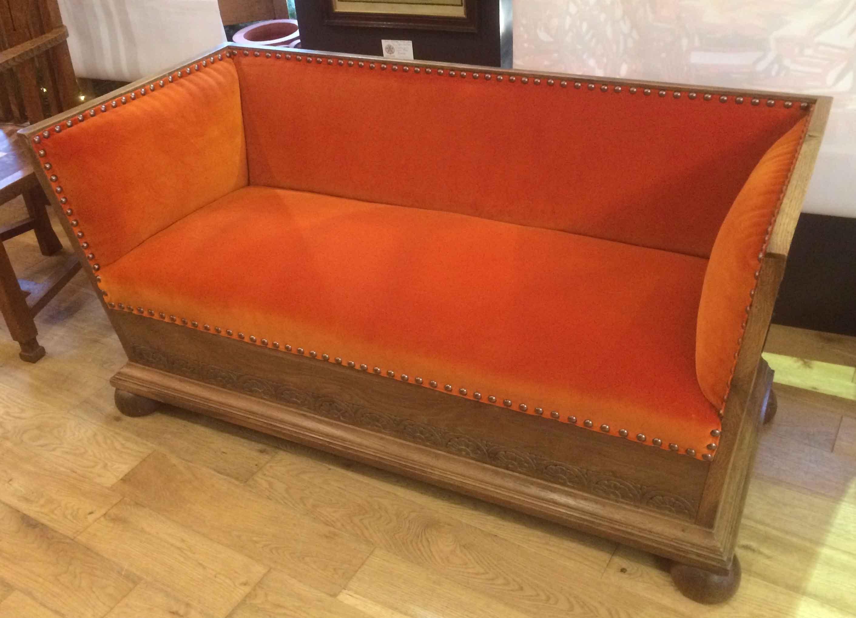 Arts and crafts oak settle upholstered in orange velvet