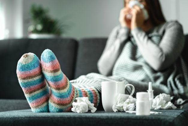 En kvinna i färgglada strumpor som snyter sig