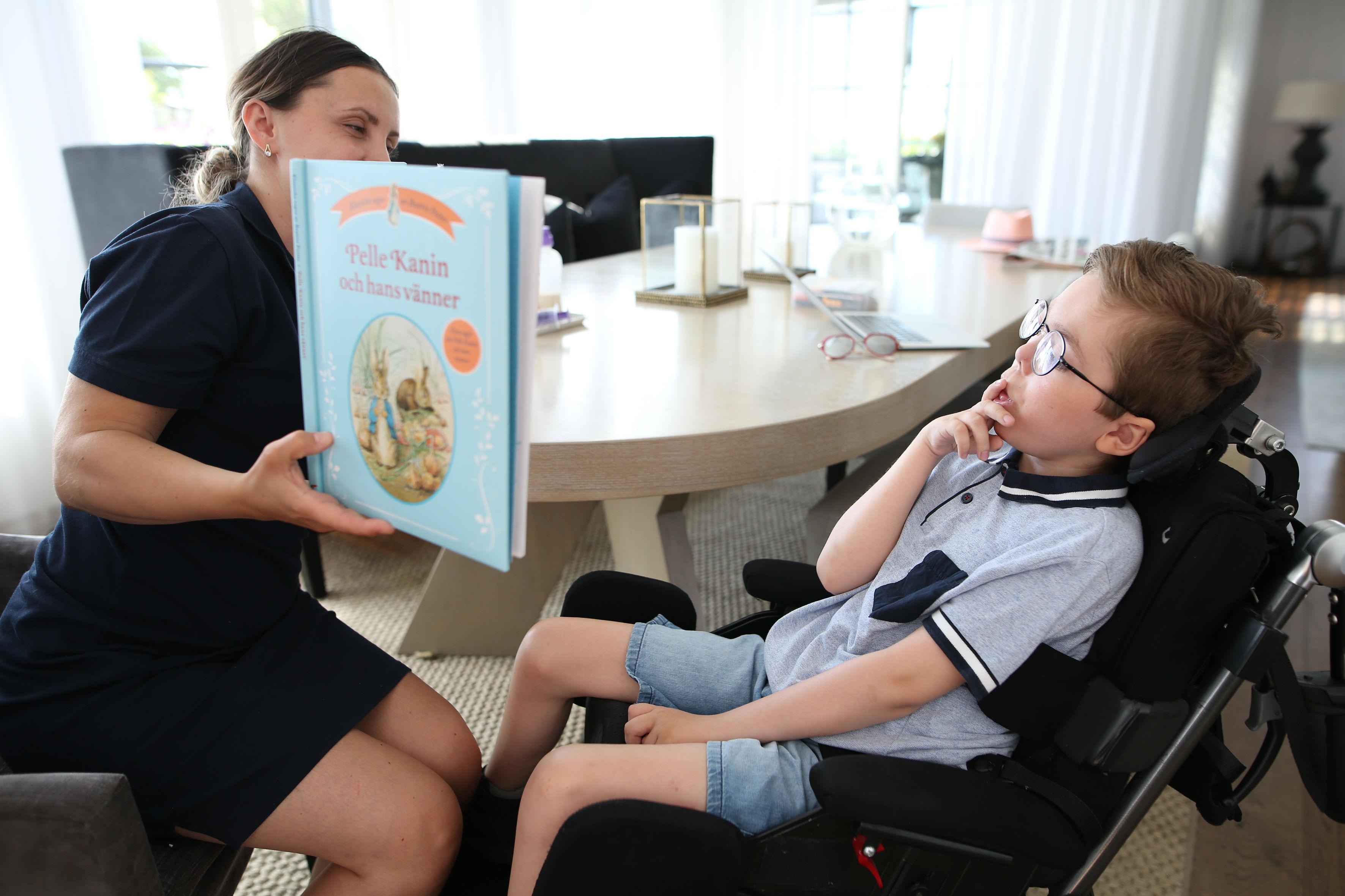 Kvinna läser bok för funktionsvarierad kille