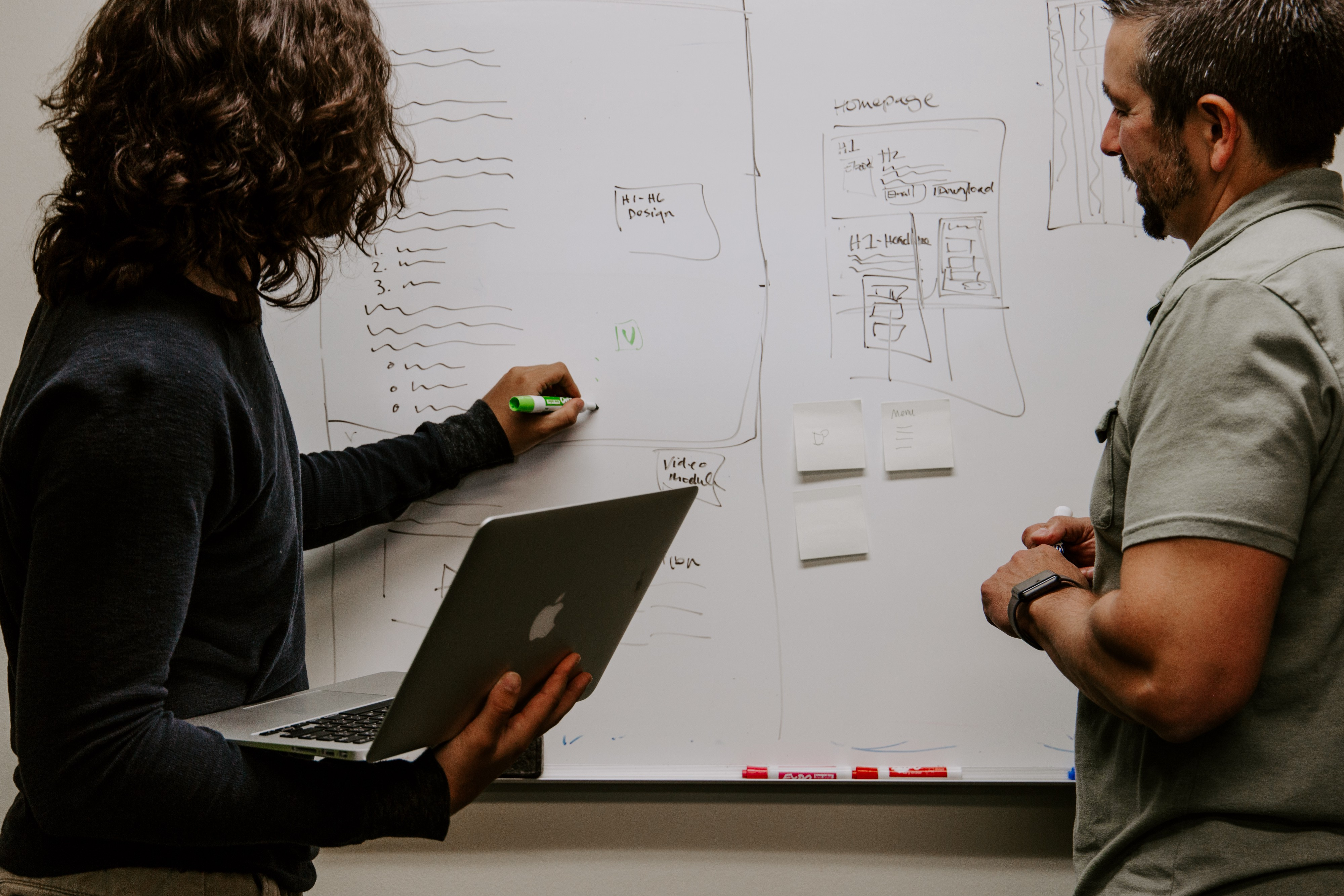 Two colleagues brainstorming on a whiteboard