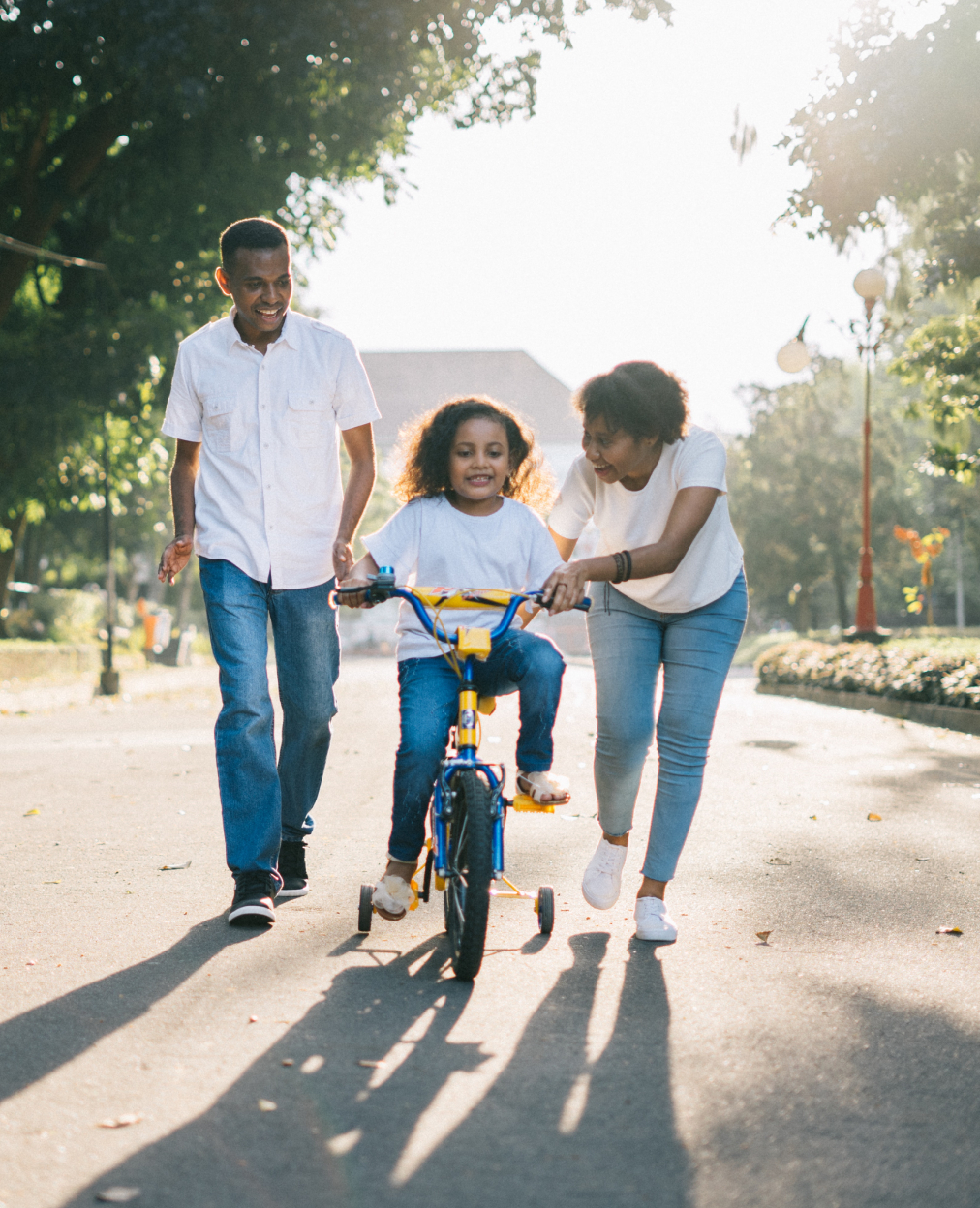 A photo of a young girl riding her bike outside in the street with her parents either side of her