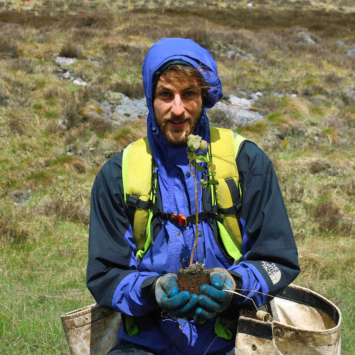 Return To Nature's founder, Will Brown, holding a sapling whilst out tree planting.