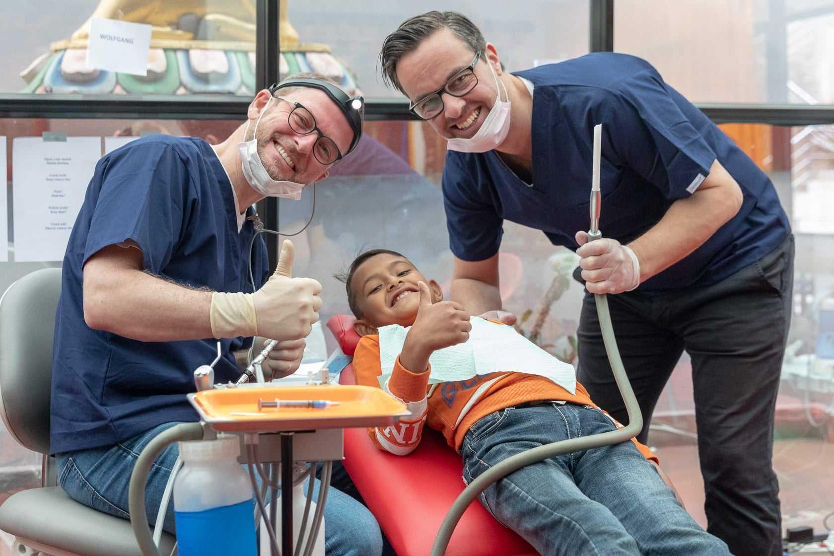 dentist1 Zahnärzte mit Kind nach erfolgreicher Behandlung im Rahmen eines gemeinnützigen Projekts