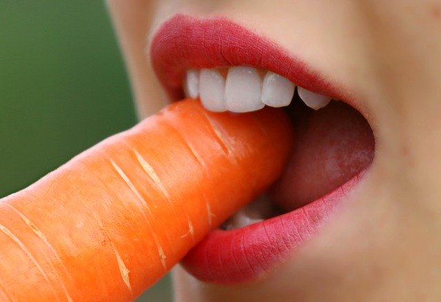Abbeißen von einer Karotte mit starken weißen Zähnen