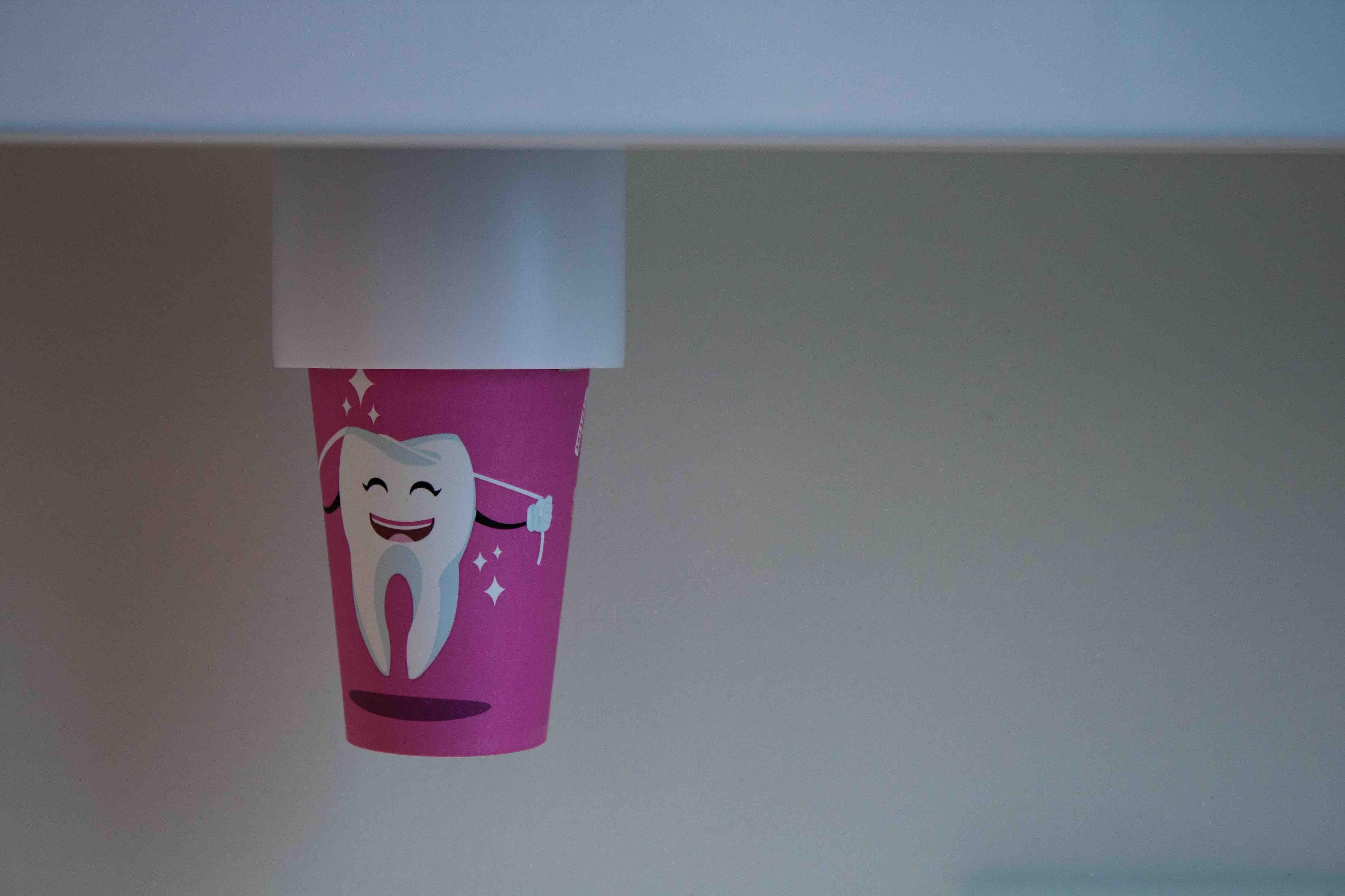 rosa Becher mit Zahn und Zahnseide