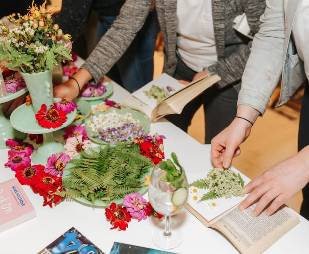 People pressing flowers into books