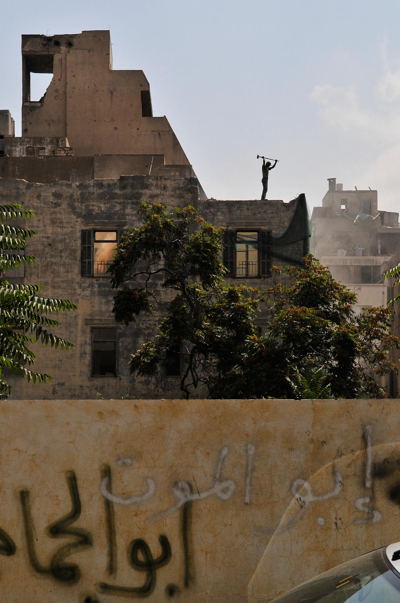 A worker destroys a traditional Lebanese building. Since 2000, Beirut has seen a wave of demolition of its traditional houses to make place for towers. Beirut, 2009.