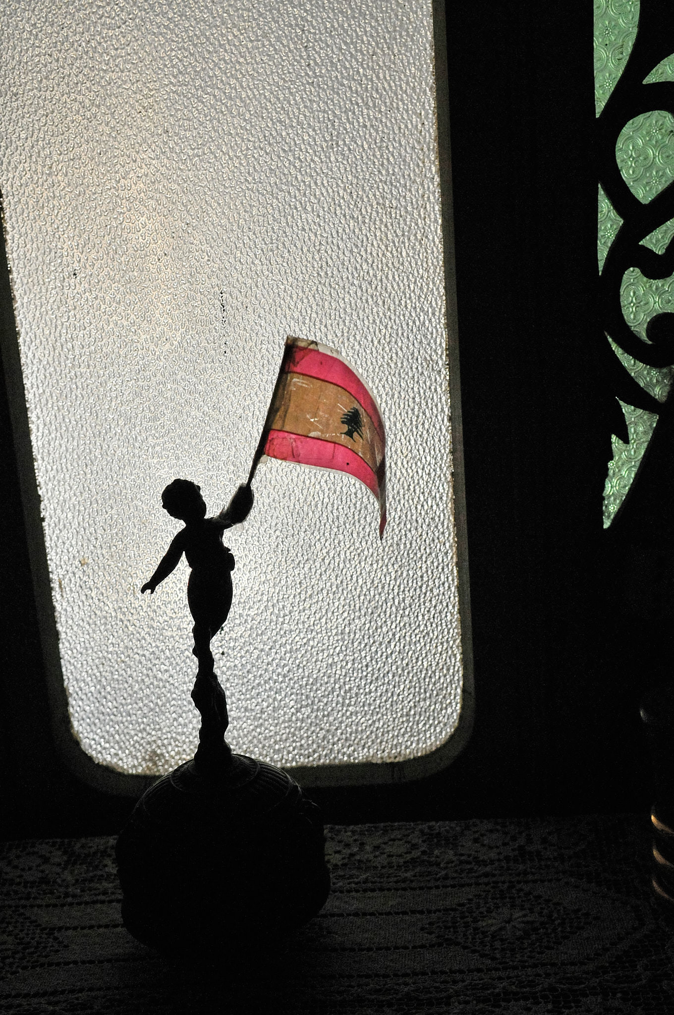 A figurine of a boy, with a broken arm repaired with scotch tape, waving a Lebanese flag. Beirut, 2009.