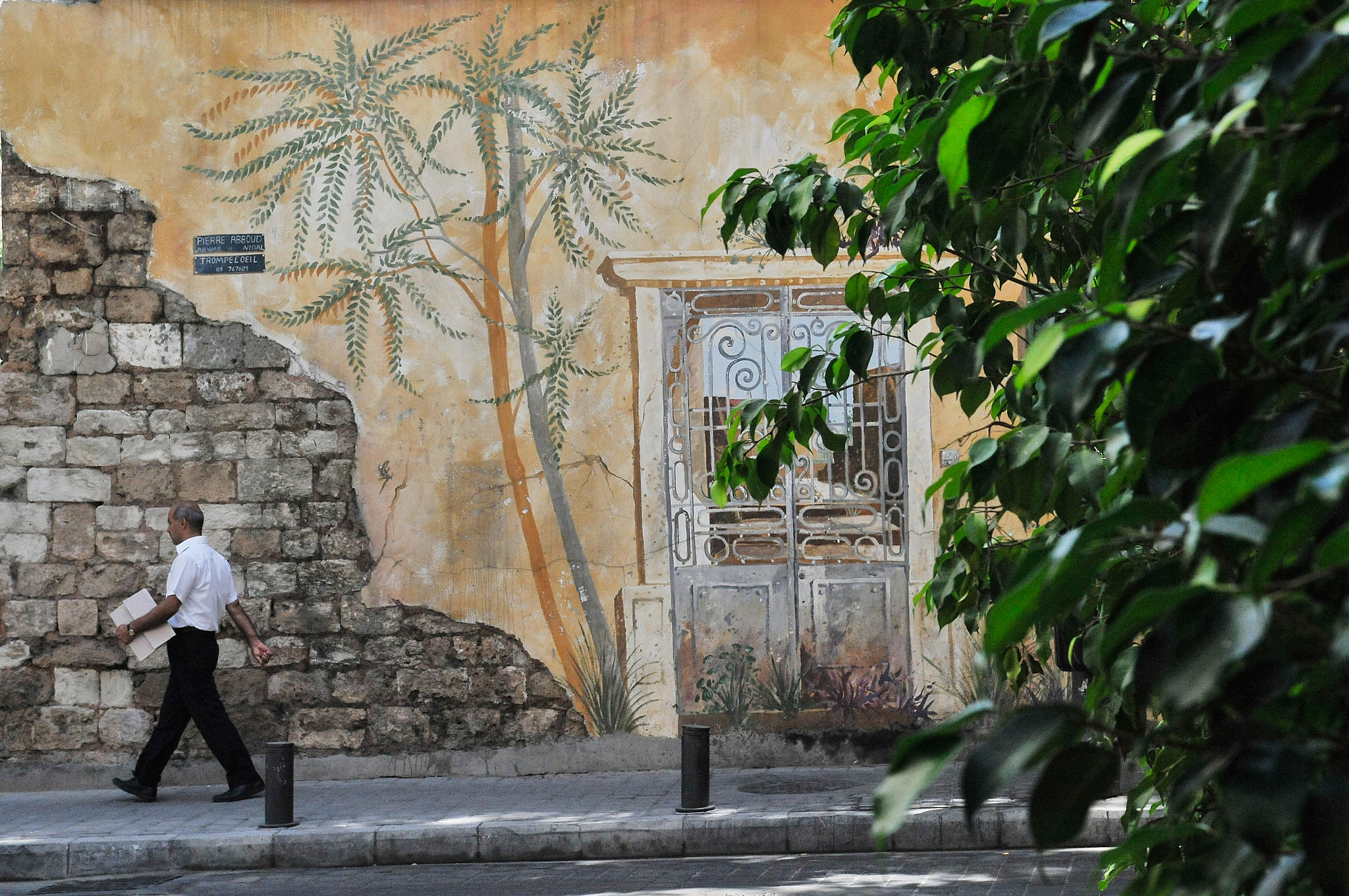 A man walks by a partially peeled wall displaying a trompe l'oeil that does not fully disguise its run-down state. Beirut, 2009.