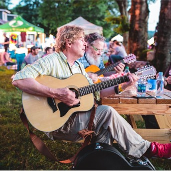 Man playing guitar at an outdoors party
