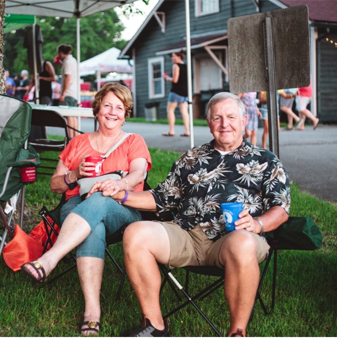 A couple relaxing in folding chairs, smiling, enjoying their beverages