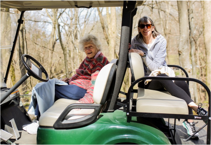 Volunteers driving tour golf cart