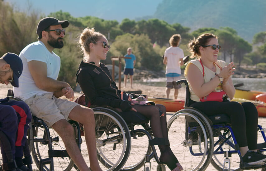 2 femmes et 2 hommes en fauteuil sur une plage
