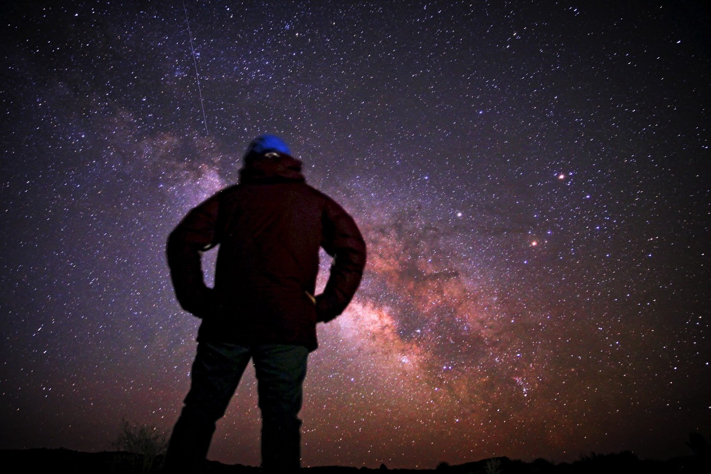 a man standing and staring at the night sky