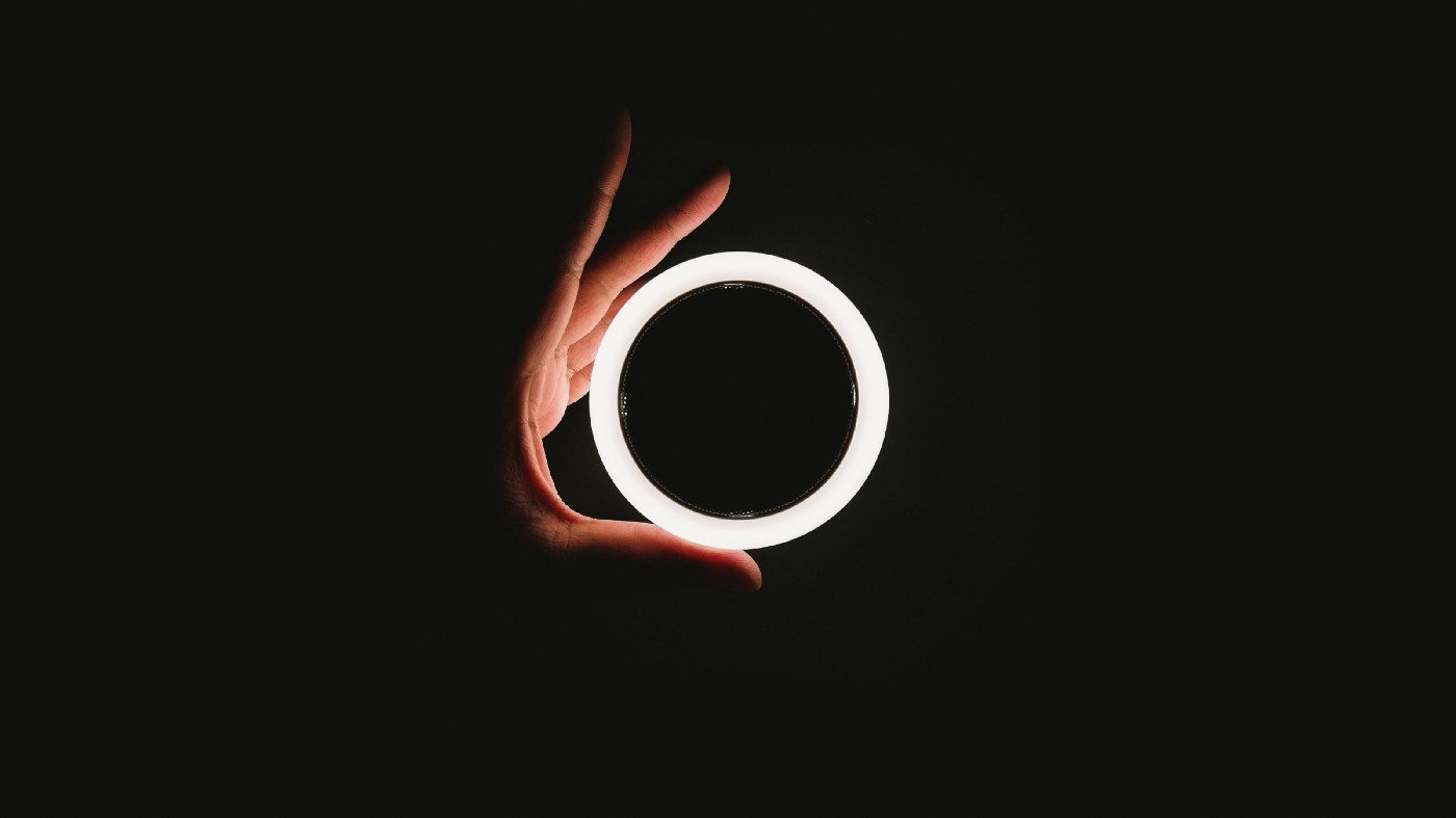 A hand holding a white circle light ring