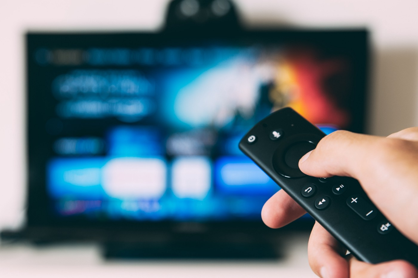 a remote control pointing a television