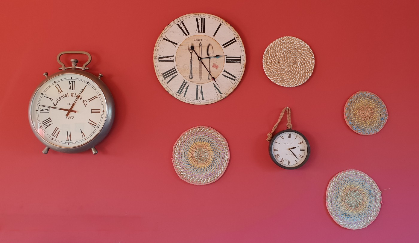 different clocks hanging on the wall