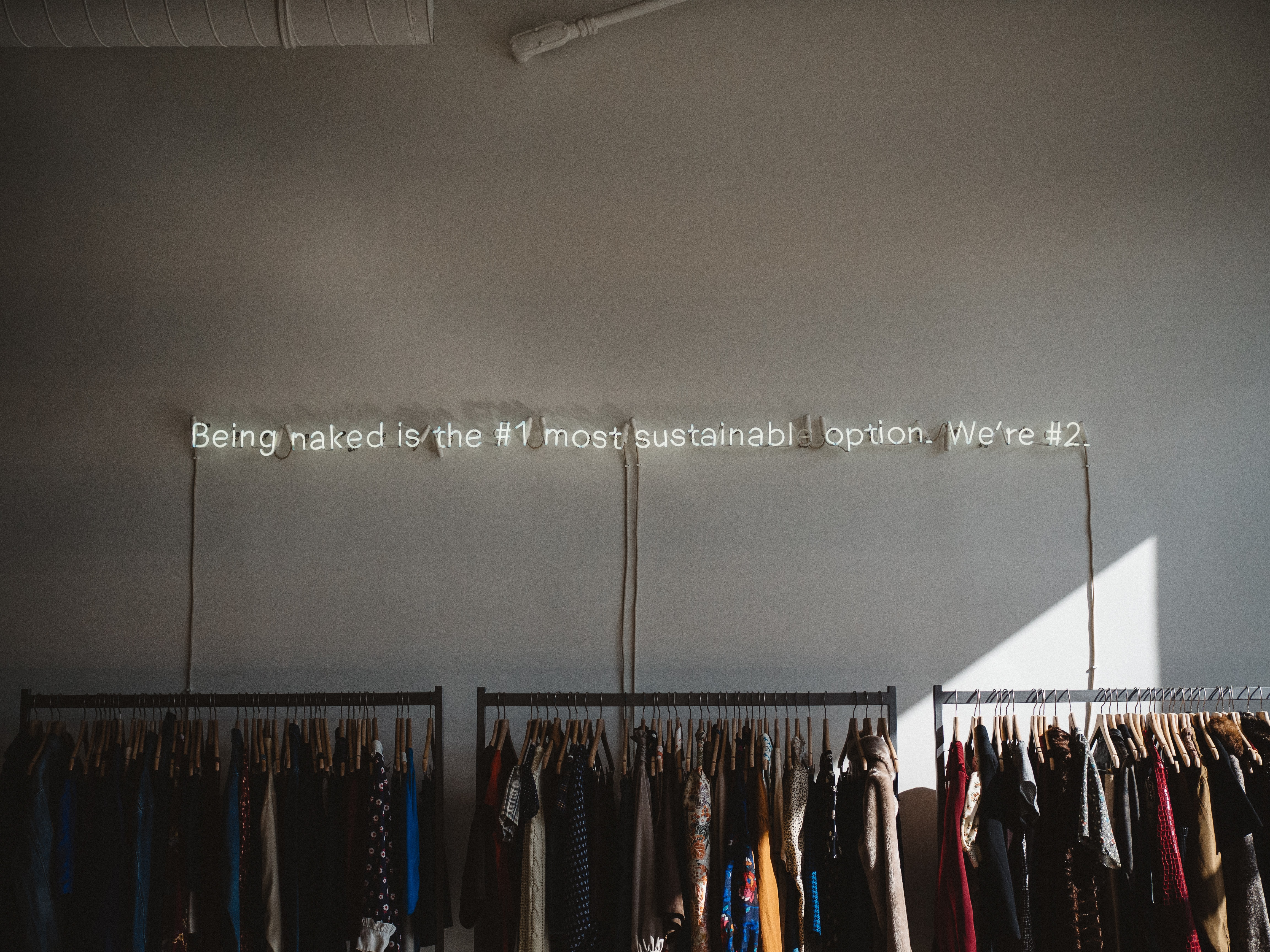 A clothes store with neon light hanging on the wall