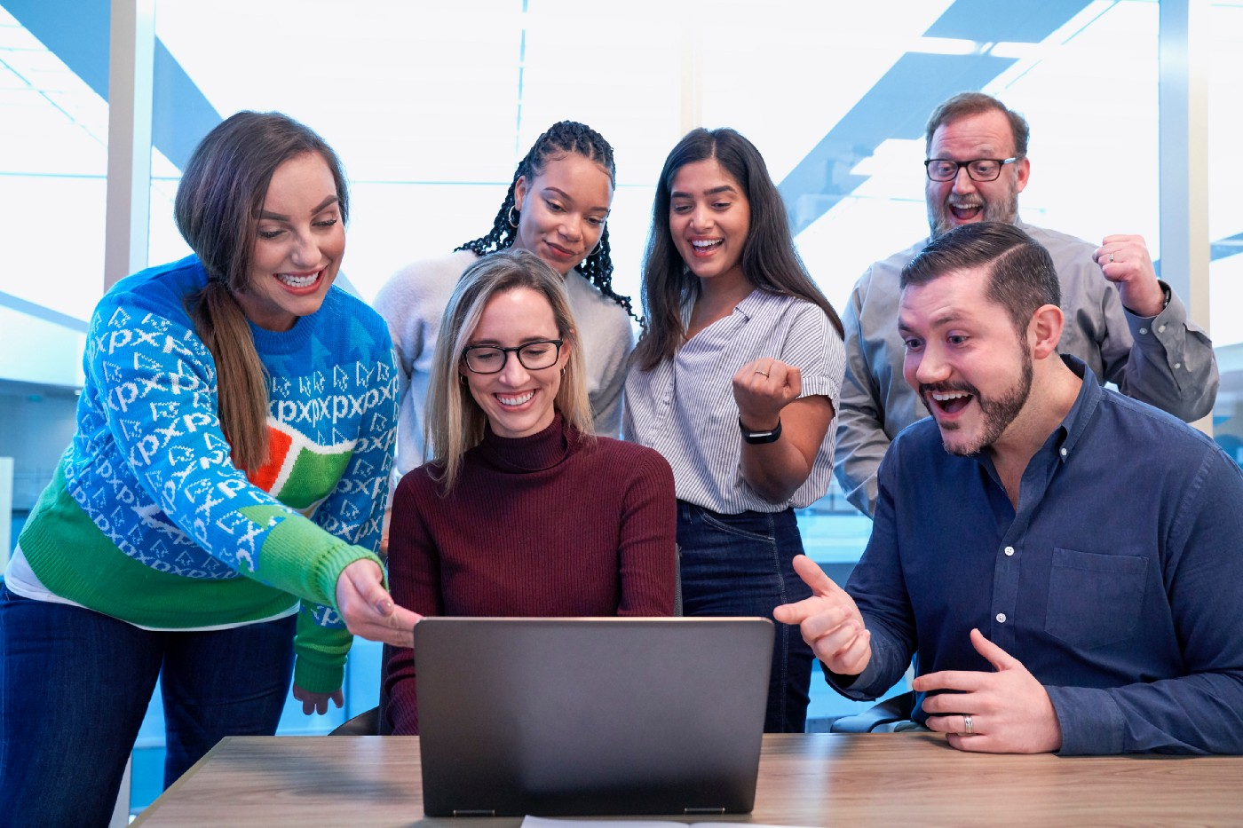 A group of office people staring at a laptop cheerfully