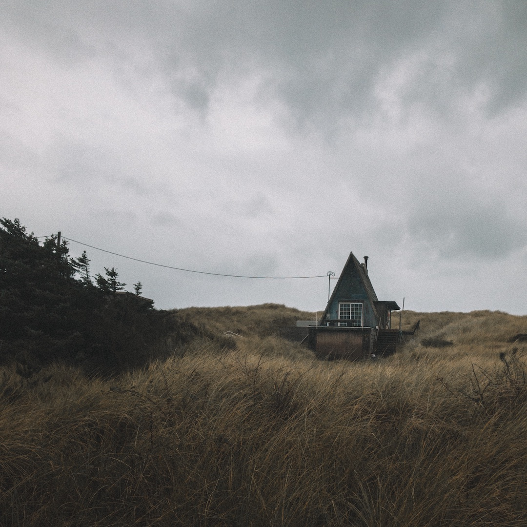 A small A-Frame house on a grassy hill on an overcast day