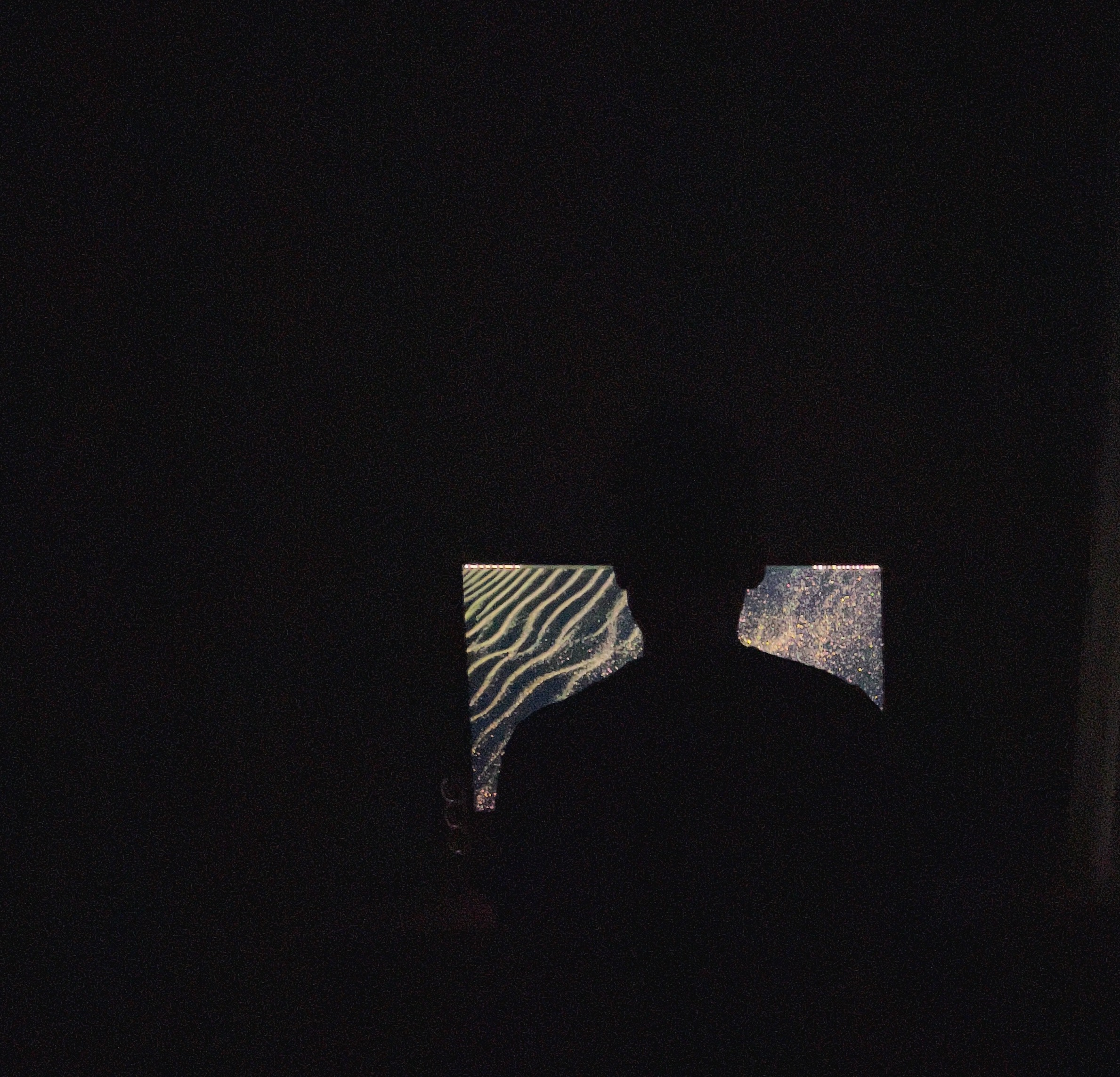 A photo behind a man sitting in the dark on his computer