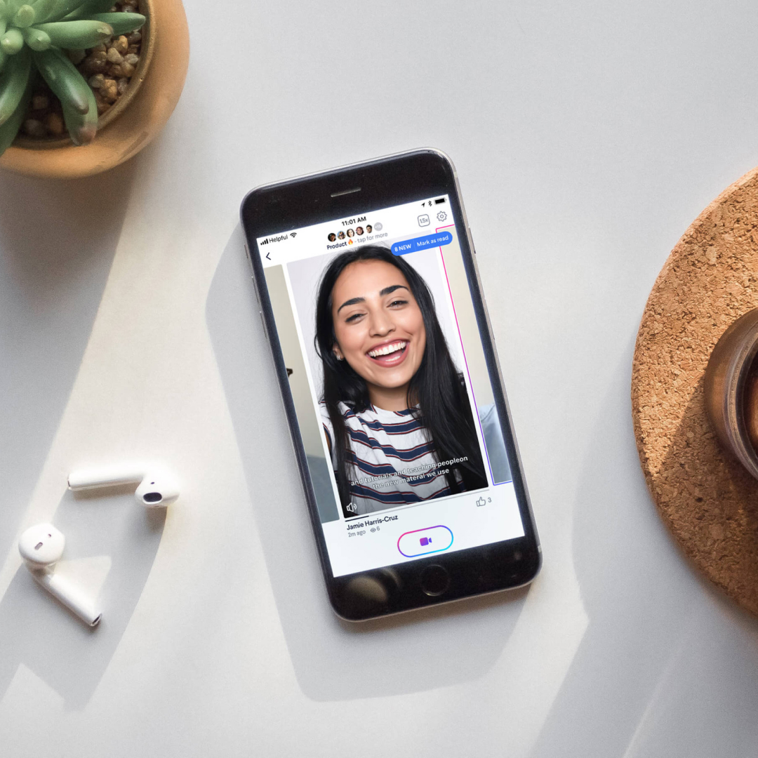 A phone and earbuds on a table with the Helpful video chat app on an iPhone