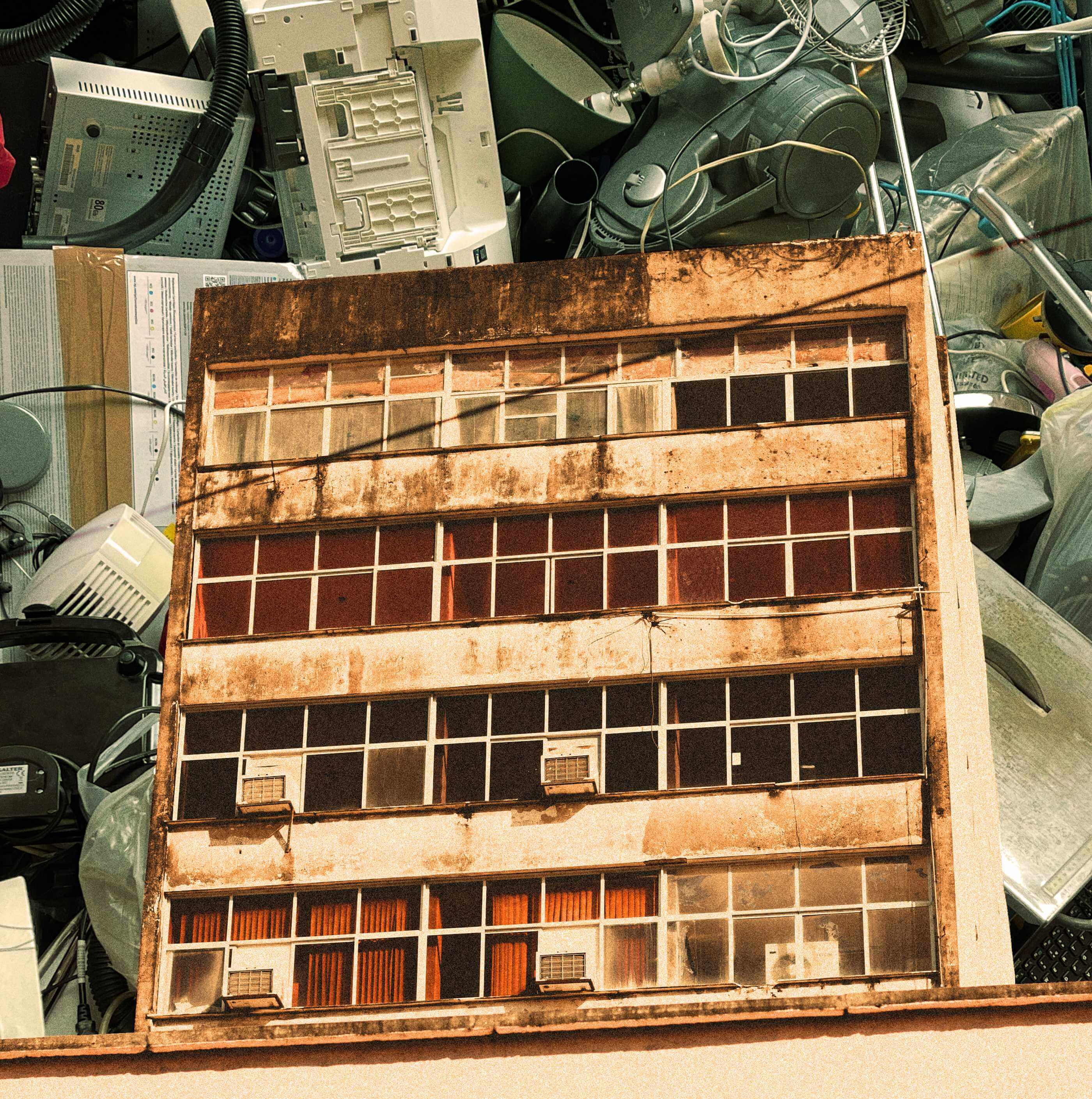 A worn down building superimposed over heaps of plastic waste
