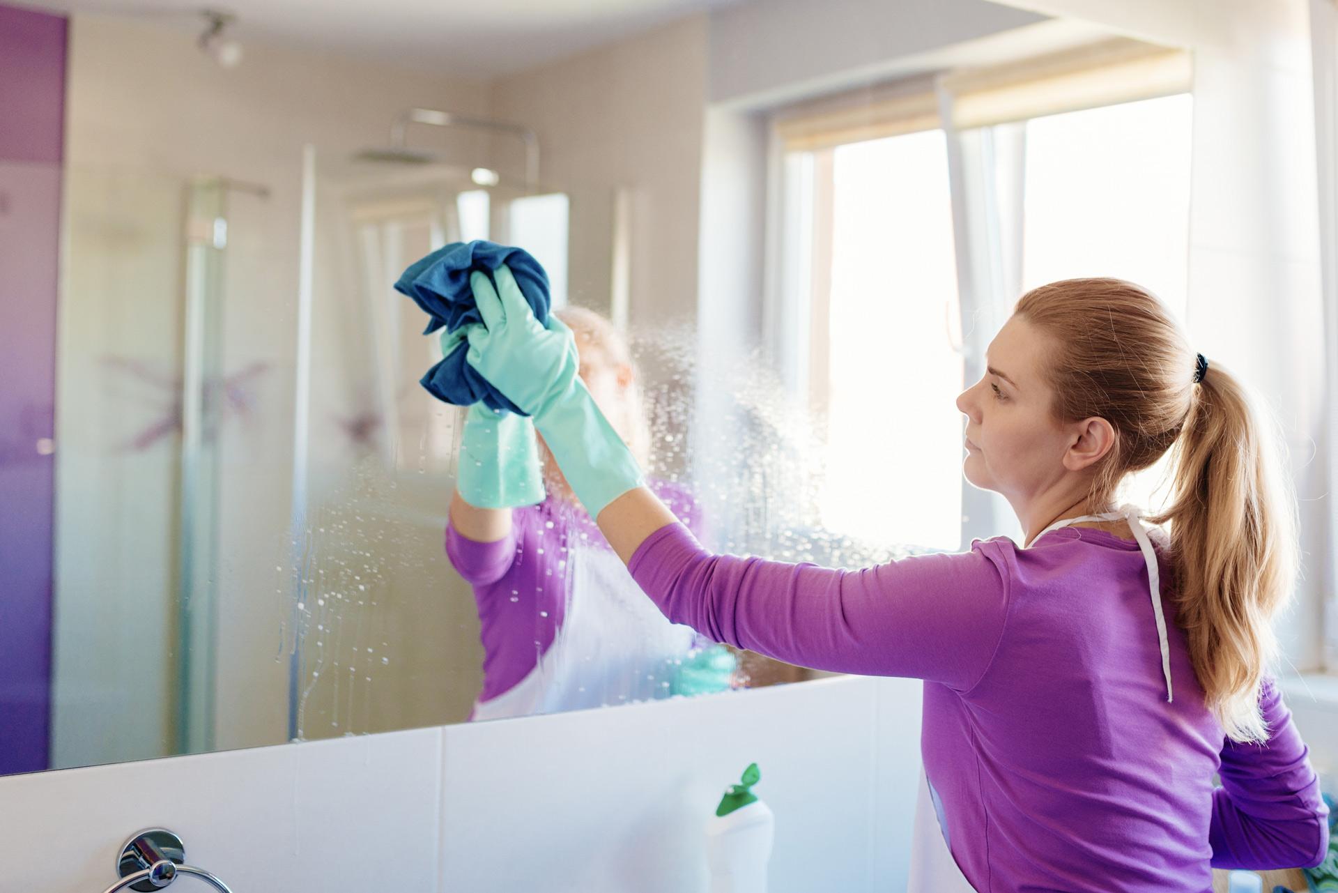 Header Bild: Putzfrau wischt mit einem Putzlappen einen Spiegel ab.