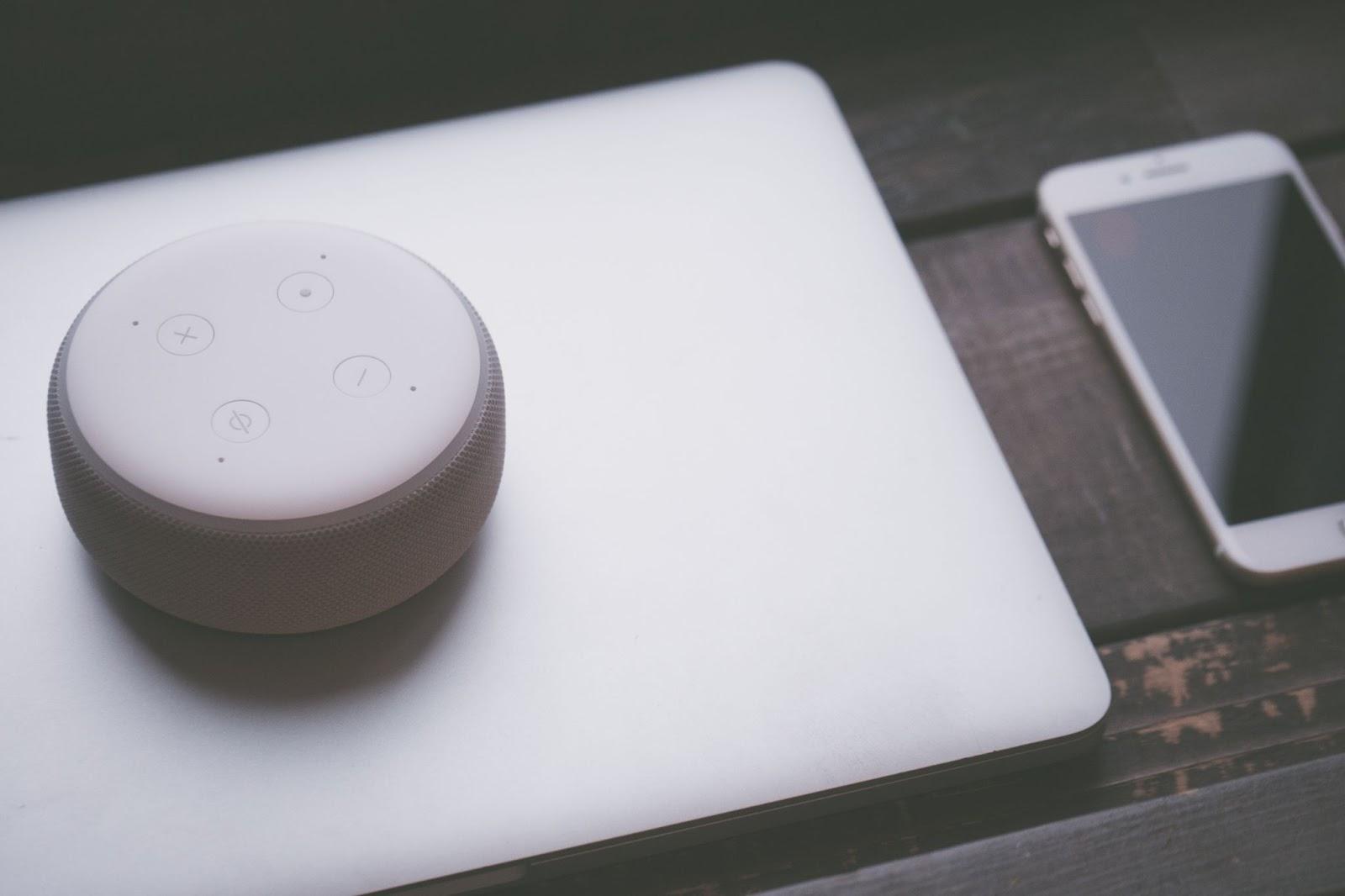 Amazon Alexa speaker sitting on a white desk.