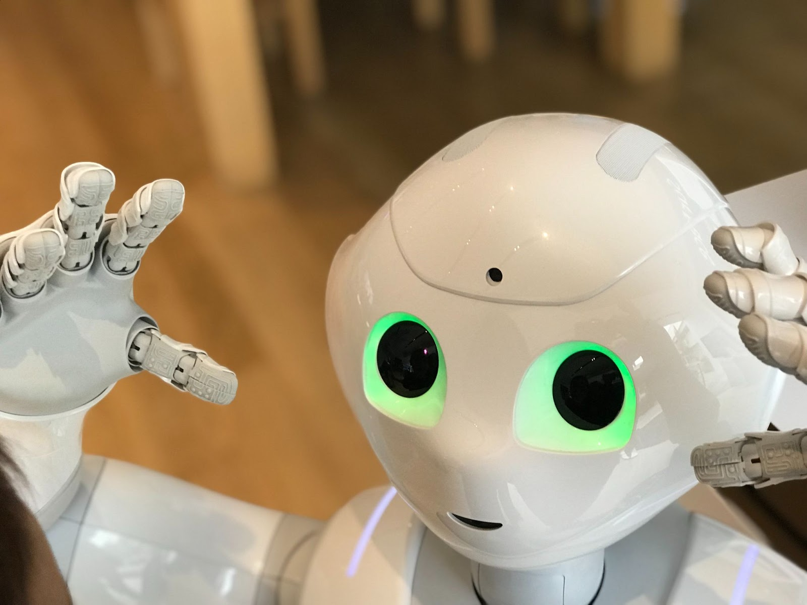 White robot holding his hands up with green glowing eyes.