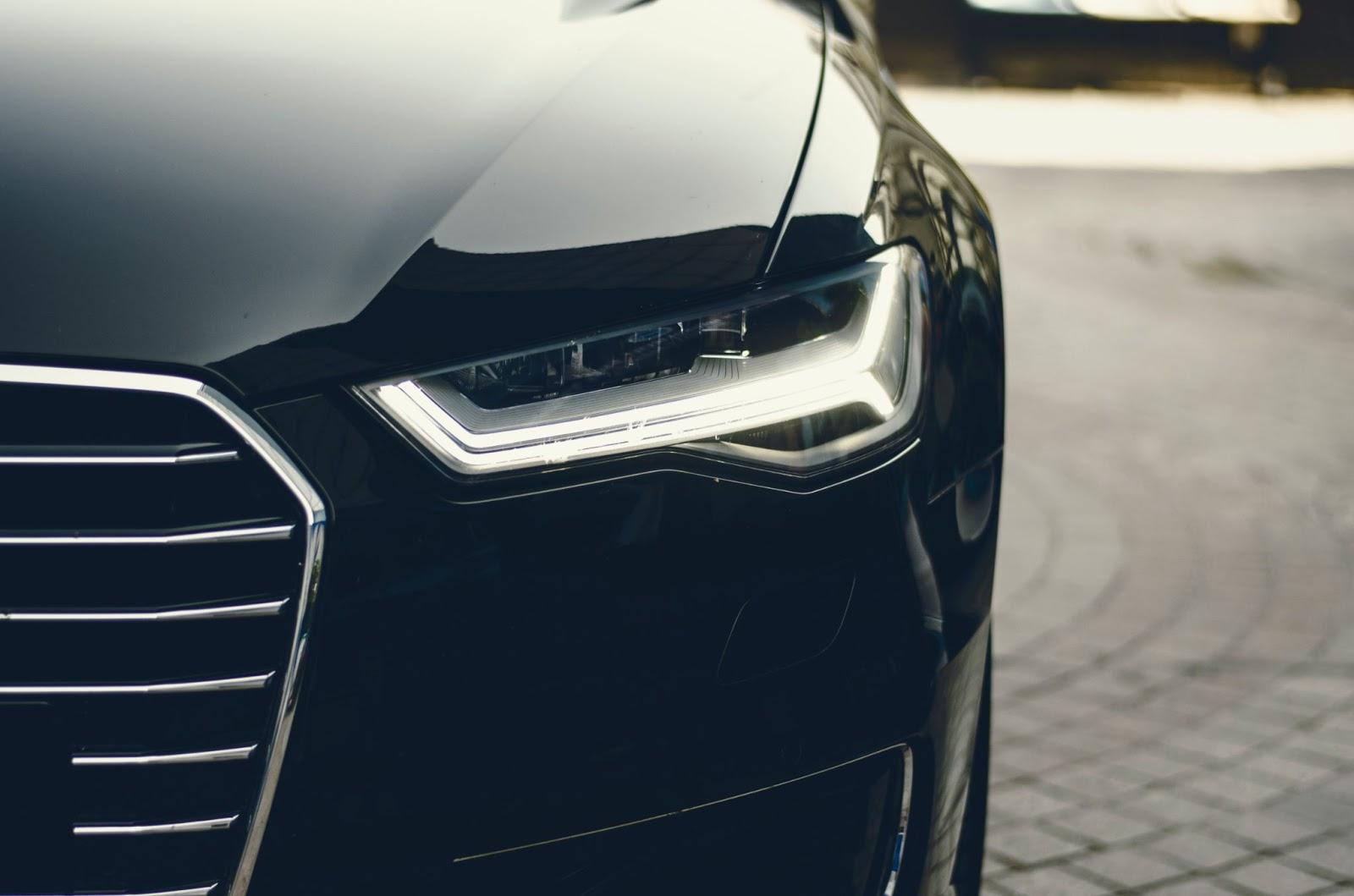 Focused imagine of headlight on a black car.