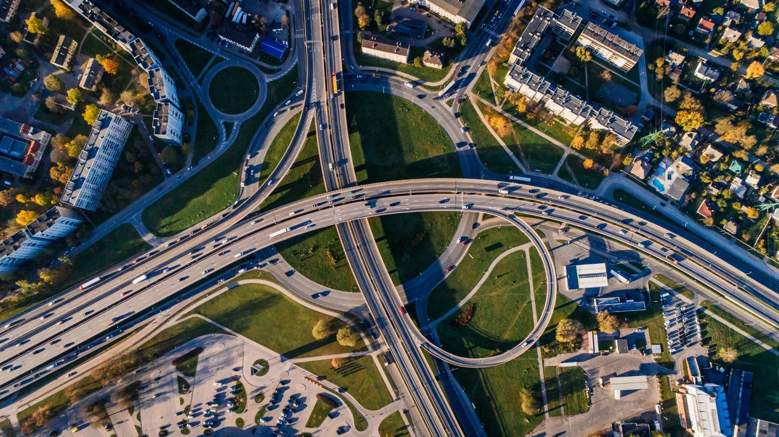 Aerial view of a highway system with on and off ramps with lots of driving cars.