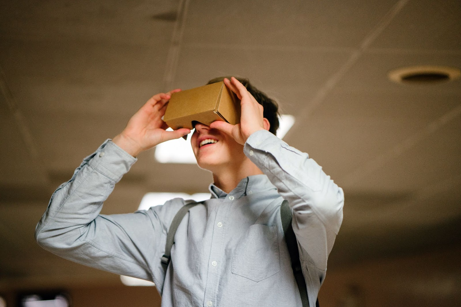 Young boy holds up a virtual reality cardboard headset to his eyes.