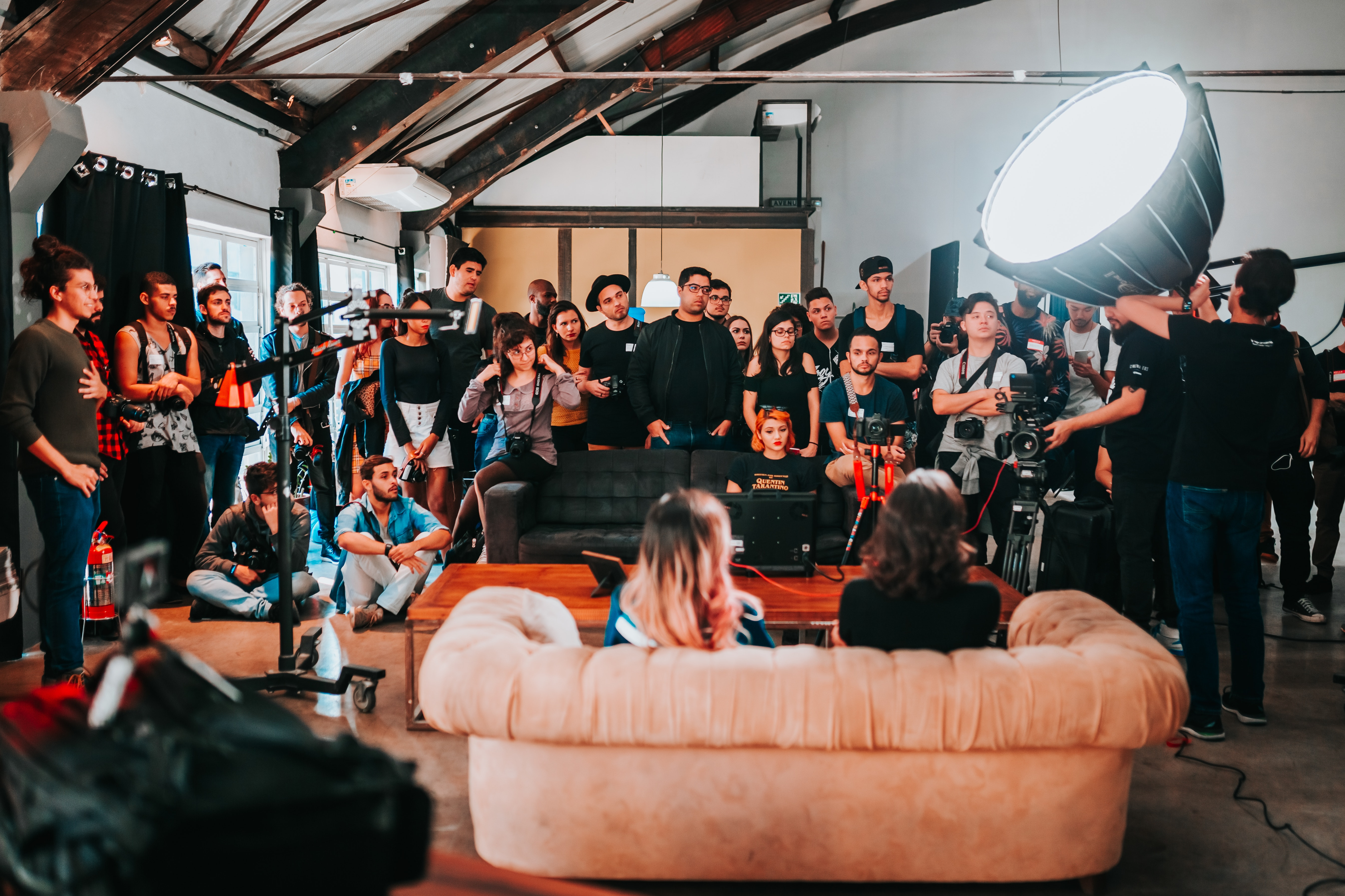An event or interview with people sitting on a couch and attendees all around listening.