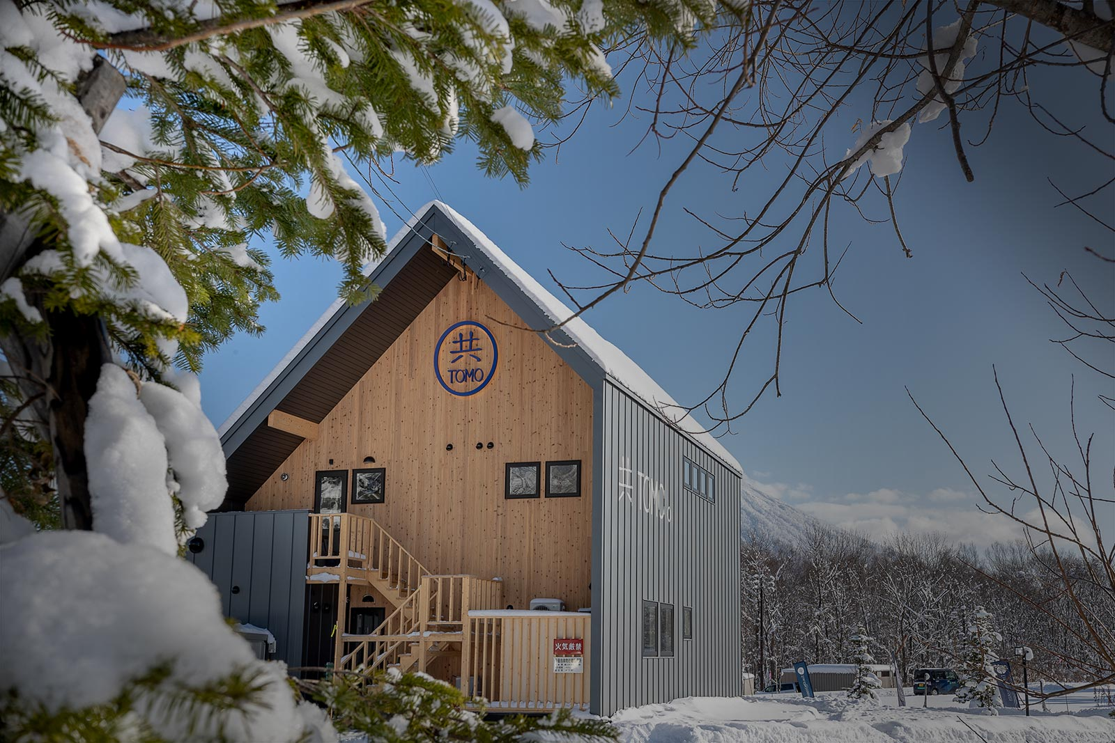Exterior view of the back of Tomo restaurant with snow and trees in view