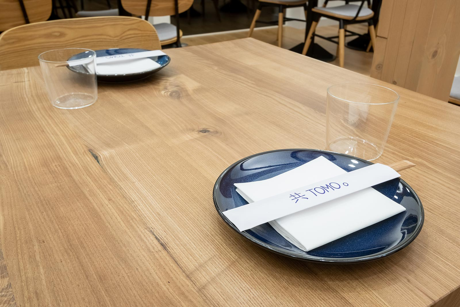 Close up of Tomo plates and branded chopstick holders on a dining table